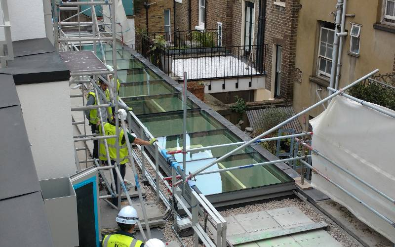 Huge electrically operated sliding glazed roof hatches for Great Portland Street, London