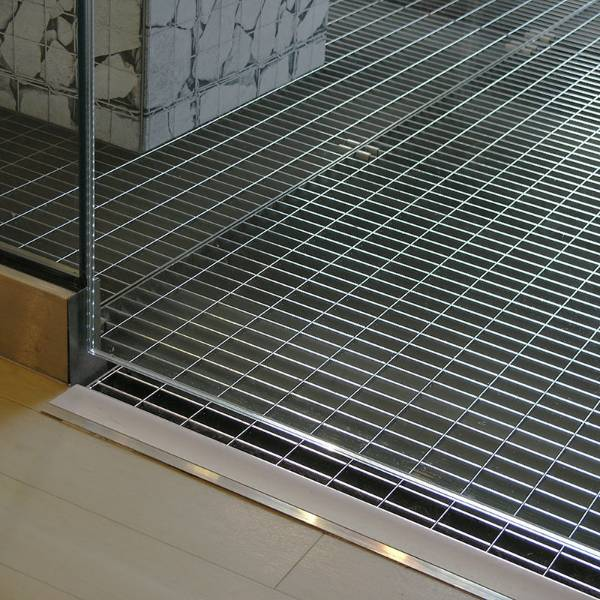 Primark - stainless steel floor grating serving as a light-well, introducing natural light to a basement shopping area