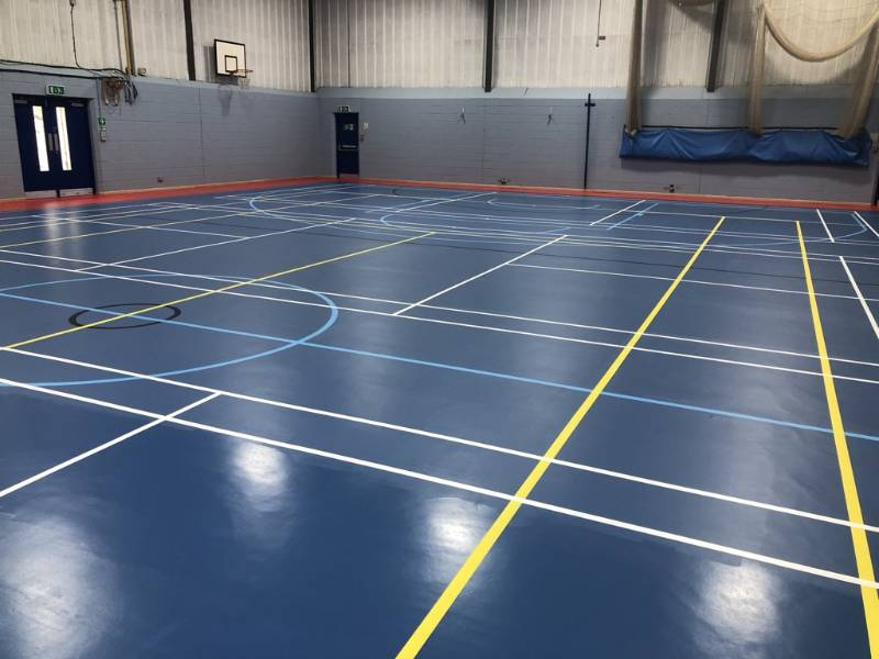 Recoating a resilient sports floor